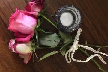 drei Rosen mit Teelicht auf Holztisch