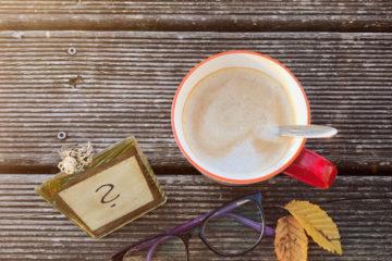 Kaffee, Brille und Blätter auf dem Boden